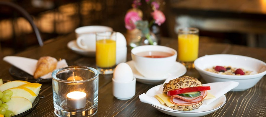 Hotel breakfast with juice, eggs, sandwich and croissants