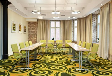 A conferenceroom with green carpeting, a brick wall and light chairs.
