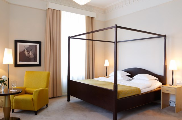 Hotel room with a bed and a yellow armchair